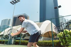 Young man playing tennis outdoors in a modern district of the city stock images