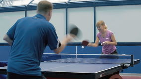 Young man playing a tennis with the woman. The camera shooting from the back of the man. The man in blue T-shirt playing a ping-pong with the young woman. The stock video footage