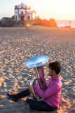 Young man playing the trumpet on the sea coast. Tuba instrument. Royalty Free Stock Image