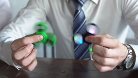 Young man playing with two fidget spinners. slow motion stock footage