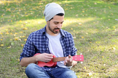 Young man playing the ukelele in a park. Stock Images