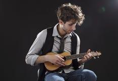 Young man playing a ukulele Royalty Free Stock Photos