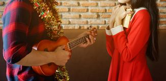 Young couple celebrate Christmas with ukulele. Young man playing ukulele after giving gift box to her girlfriend while smile girl happy to listen the song Royalty Free Stock Images