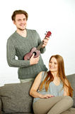 Young man playing ukulele to his girlfriend Stock Images
