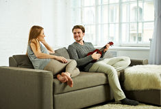 Young man playing ukulele to his girlfriend Royalty Free Stock Image