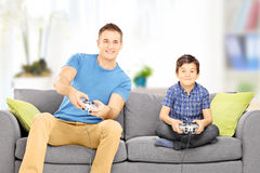 Young man playing video game with his younger cousin Stock Photo