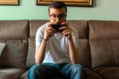 Young man playing video game holding wireless controller stock image