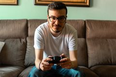 Young man playing video game holding wireless controller royalty free stock images