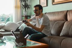 Young man playing video game holding wireless controller stock images
