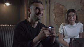 Young man playing the video game in the loft style room sitting on the sofa with his girlfriend smiling. The guy. Fighting using joystick, girl sitting near stock video