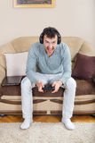 Young man playing video games with wireless Bluetooth joystick Stock Photo