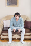 Young man playing video games with wireless Bluetooth joystick Stock Images