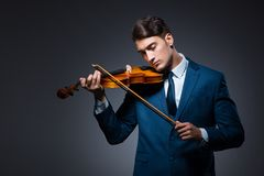 The young man playing violin in dark room. Young man playing violin in dark room Stock Photography