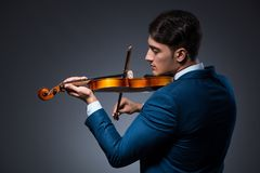 The young man playing violin in dark room Stock Images