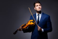 The young man playing violin in dark room Stock Photo