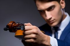 The young man playing violin in dark room. Young man playing violin in dark room Stock Photos