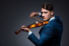 The young man playing violin in dark room. Young man playing violin in dark room Stock Images