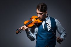 The young man playing violin in dark room. Young man playing violin in dark room Royalty Free Stock Photos