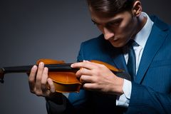 The young man playing violin in dark room. Young man playing violin in dark room Royalty Free Stock Photography