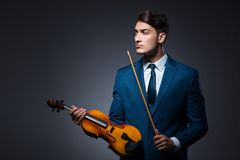 The young man playing violin in dark room. Young man playing violin in dark room Royalty Free Stock Photo