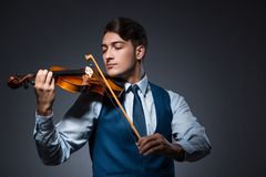 The young man playing violin in dark room. Young man playing violin in dark room Stock Photo