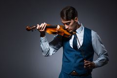 The young man playing violin in dark room. Young man playing violin in dark room Royalty Free Stock Images
