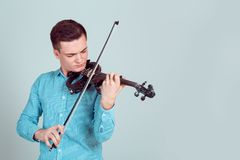 Young man playing violin stock images