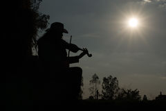 A young man playing the violin The straw in the field The golden Stock Photo