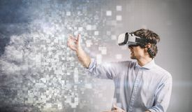Young man playing in VR goggles. Graphic design. stock photos