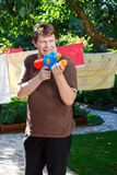 Young man playing with water gun in summer garden Stock Image