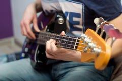 Young man plays bass guitar Royalty Free Stock Image