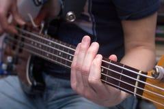 Young man plays bass guitar Stock Photography
