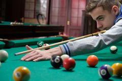Young man plays billiards. hobbies. And vacations on a day off Royalty Free Stock Photography