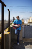 Young man plays electric guitar on roof terrace Royalty Free Stock Photography