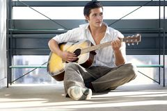 Young man plays guitar. Young casual man playing guitar Stock Photography