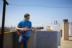 Young man plays guitar on roof terrace Stock Images