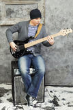 Young man plays guitar sitting on amplifier Royalty Free Stock Photography