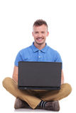 Young man plays on laptop. Casual young man holding his laptop while sitting on the floor with his feet crossed and smiling for the camera. on a white background Royalty Free Stock Photo