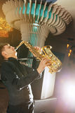 Young man plays a musical instrument saxophone Stock Image