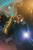 Young man plays a musical instrument saxophone Stock Photos