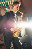 Young man plays a musical instrument saxophone Royalty Free Stock Images