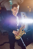 Young man plays a musical instrument saxophone Royalty Free Stock Photos