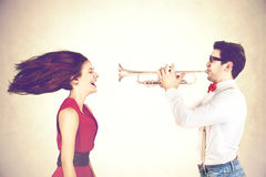 Young man plays with power his trumpet messing the hair of his girlfriend Stock Photography