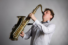 Young man plays the saxophone. Royalty Free Stock Images