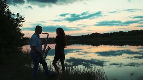 The young man plays the saxophone for girl at sunset. stock video