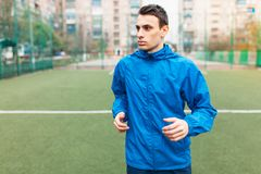 A young man plays sports, runs on the football field. The guy works in the open, fresh air. stock images