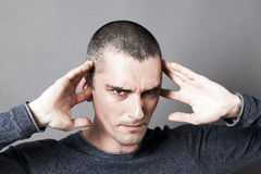 Young man plugging ears to avoid listening to problems Stock Photos