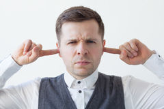 Young man plugs his ears with his hands. royalty free stock photography