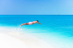 Young man plunging into the turquoise sea Stock Images