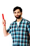Young man pointing with big red pencil. Royalty Free Stock Image